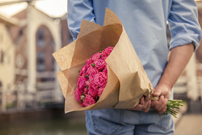 A man holding a bouquet of flowers behind his back.