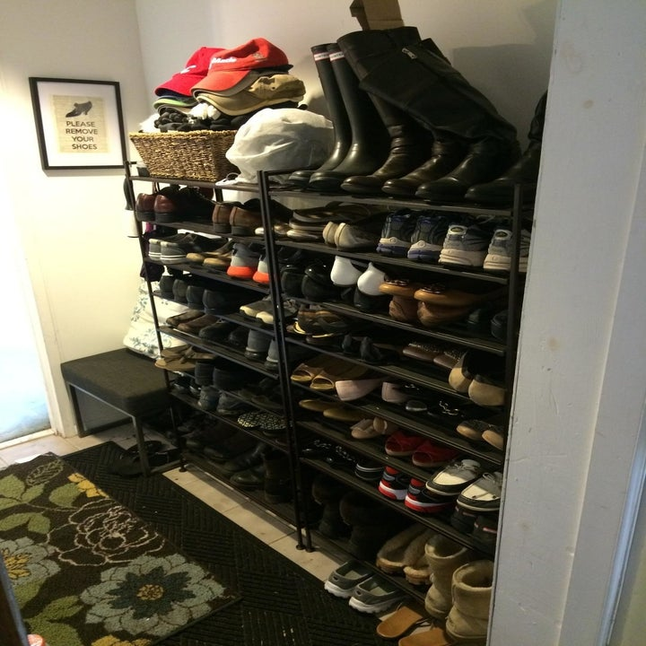 A customer's foyer lined ceiling to floor with Seville Classics 3-Tier Stackable shoe racks filled with shoes