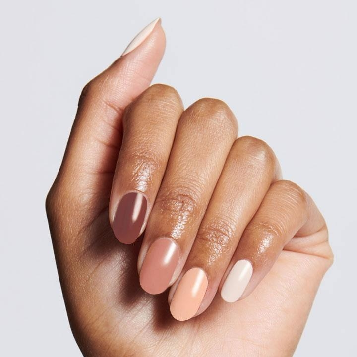 A model's hand with each nail painted a different warm brown shade to create an ombré effect