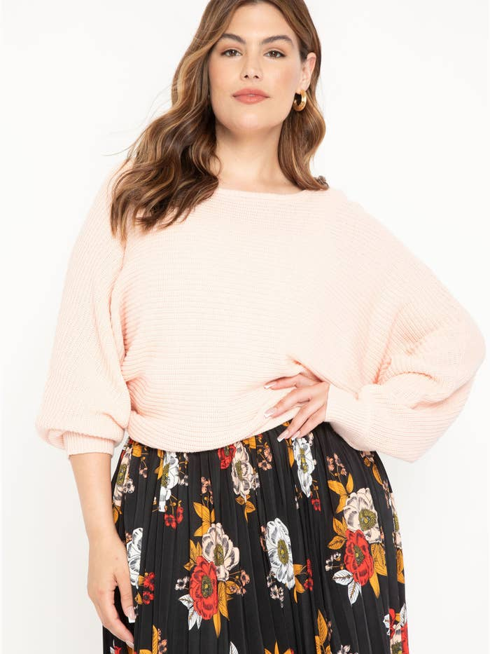 person wearing a light pink sweater over a floral skirt