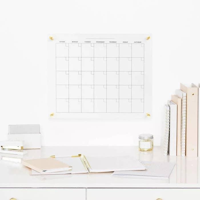 The glass dry erase calendar hung above desk