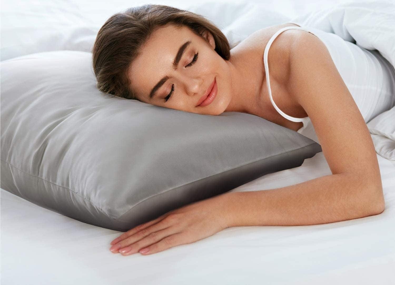 A model sleeping on a grey satin pillowcase