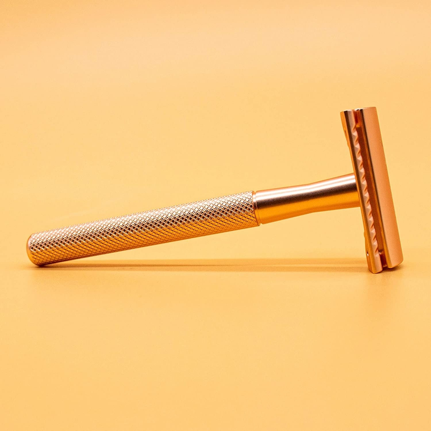 A rose gold razor on a table