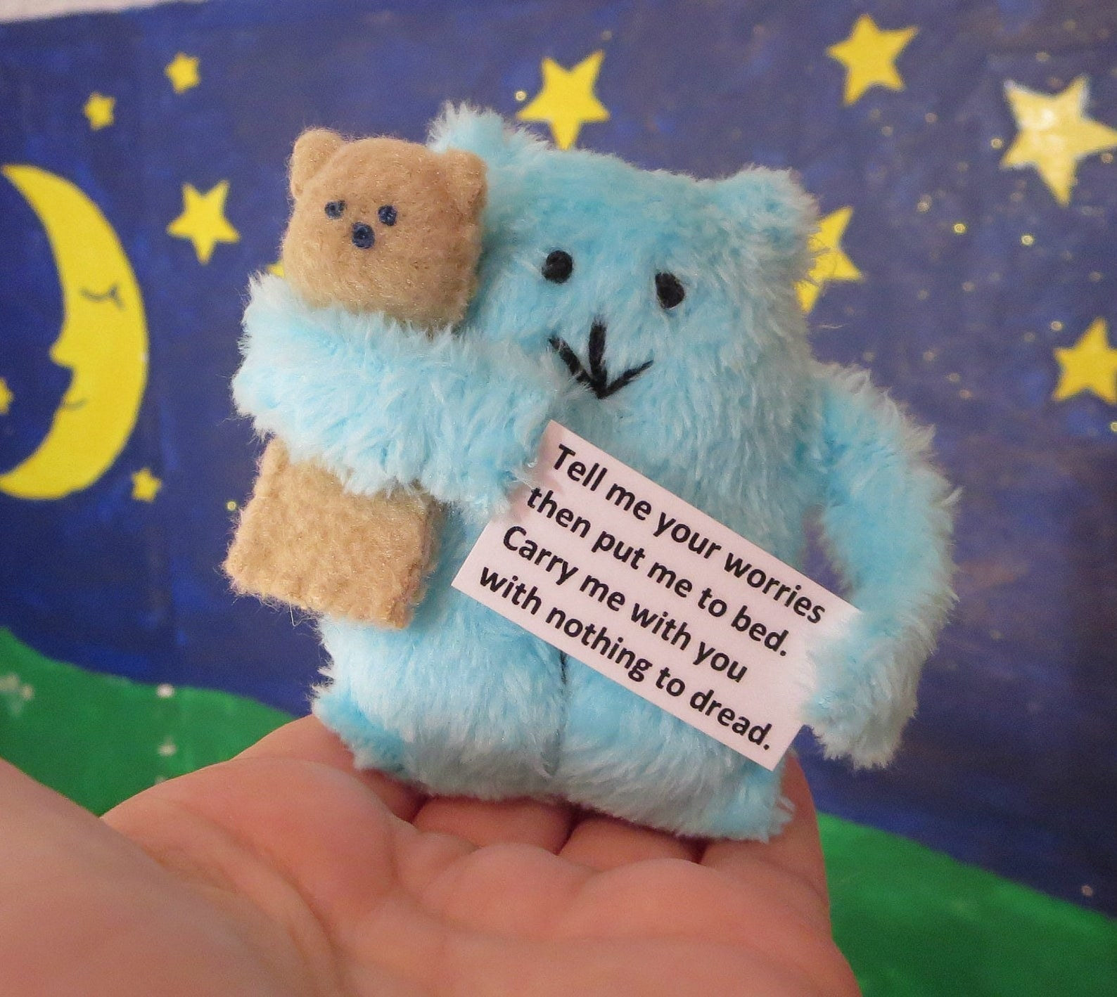 A blue monster holding a teddy bear with a poem in its hand