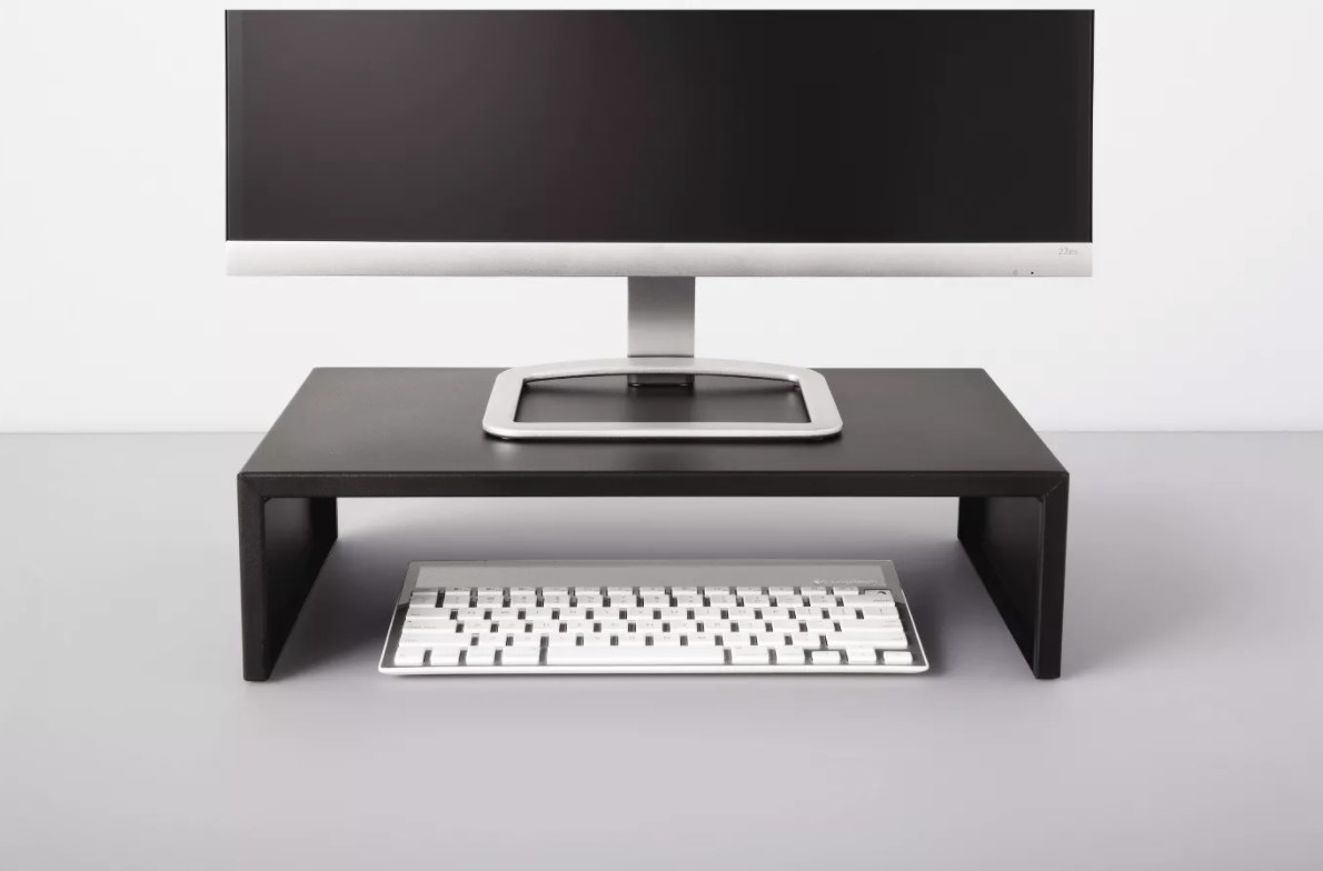 Monitor stand in black resting on desk