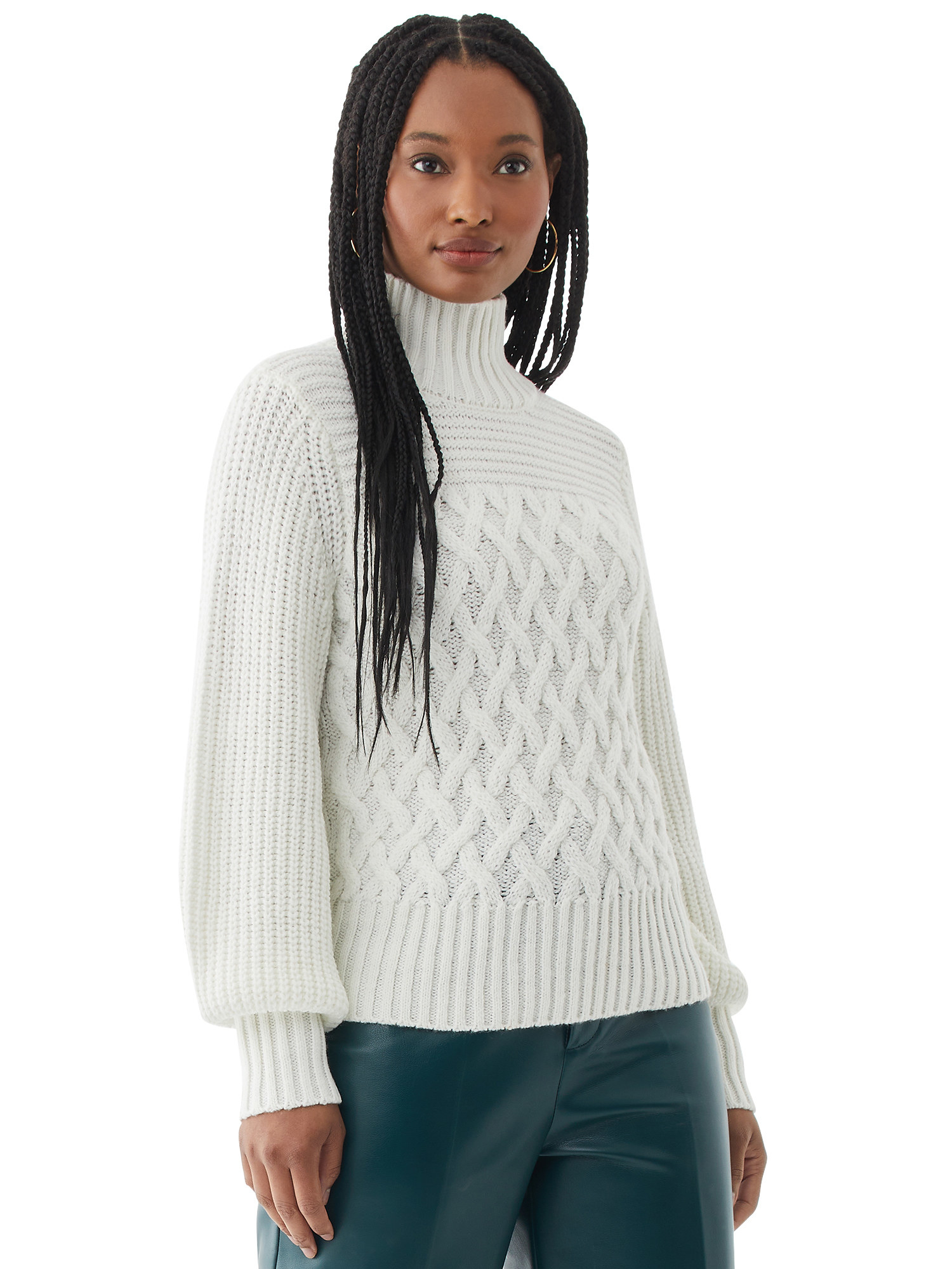 person wearing a white cable knit turtleneck sweater and dark leather pants