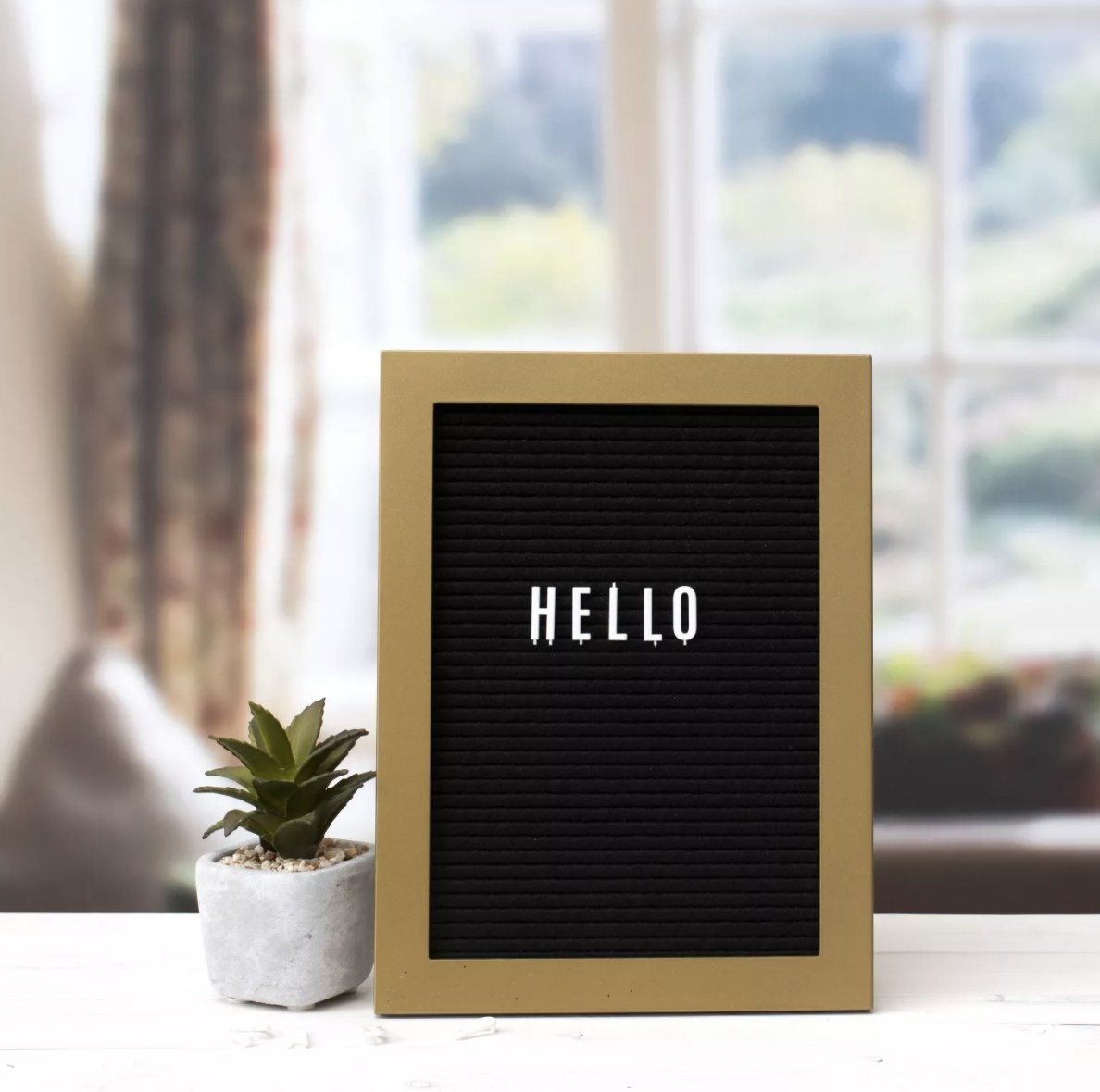 """Black letterboard set with white letters featuring """"hello"""" on board"""