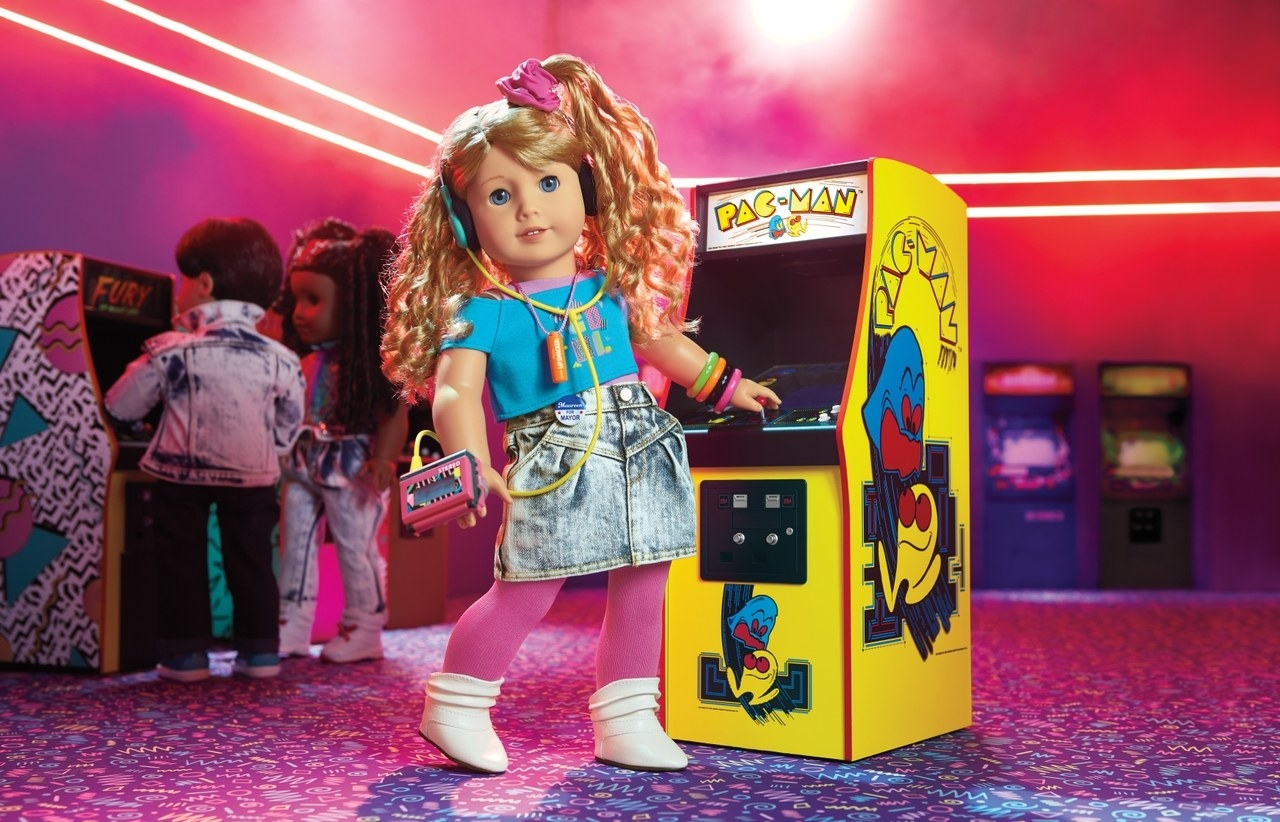 Courtney in a jean skirt and crop top and scrunchie at an arcade playing PAC-MAN