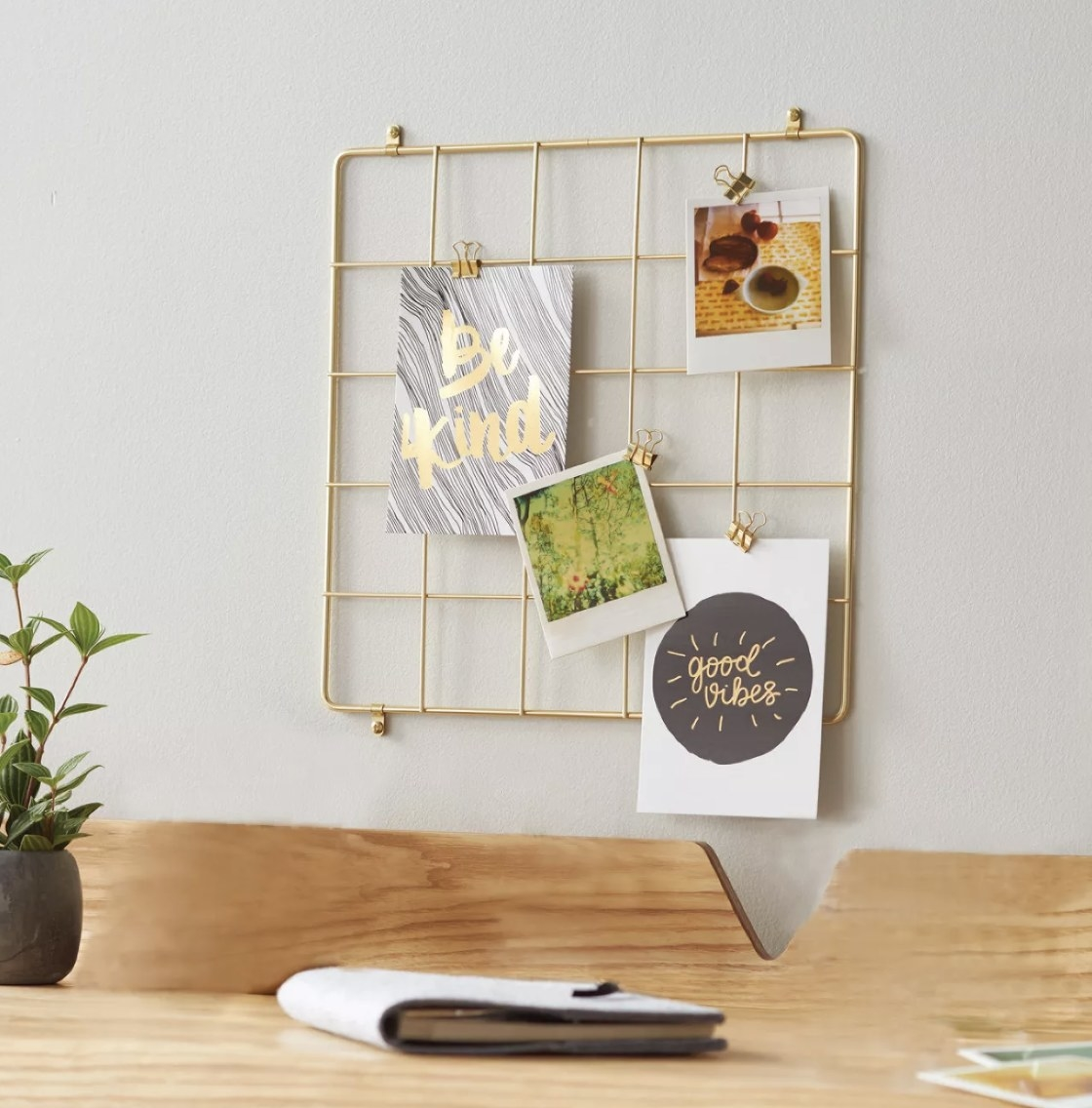 Gold grid wall organizer with clips hung above desk space