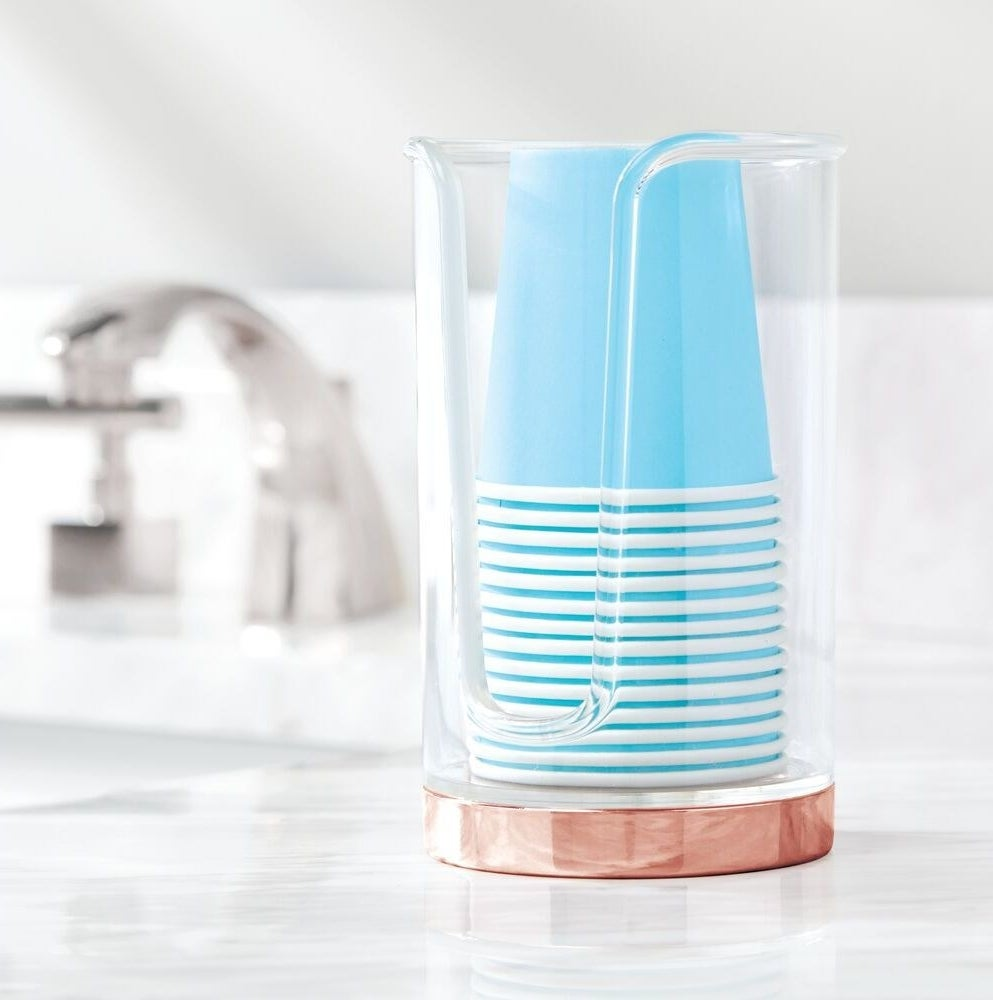 The clear and rose gold cup holder and dispenser with cups inside