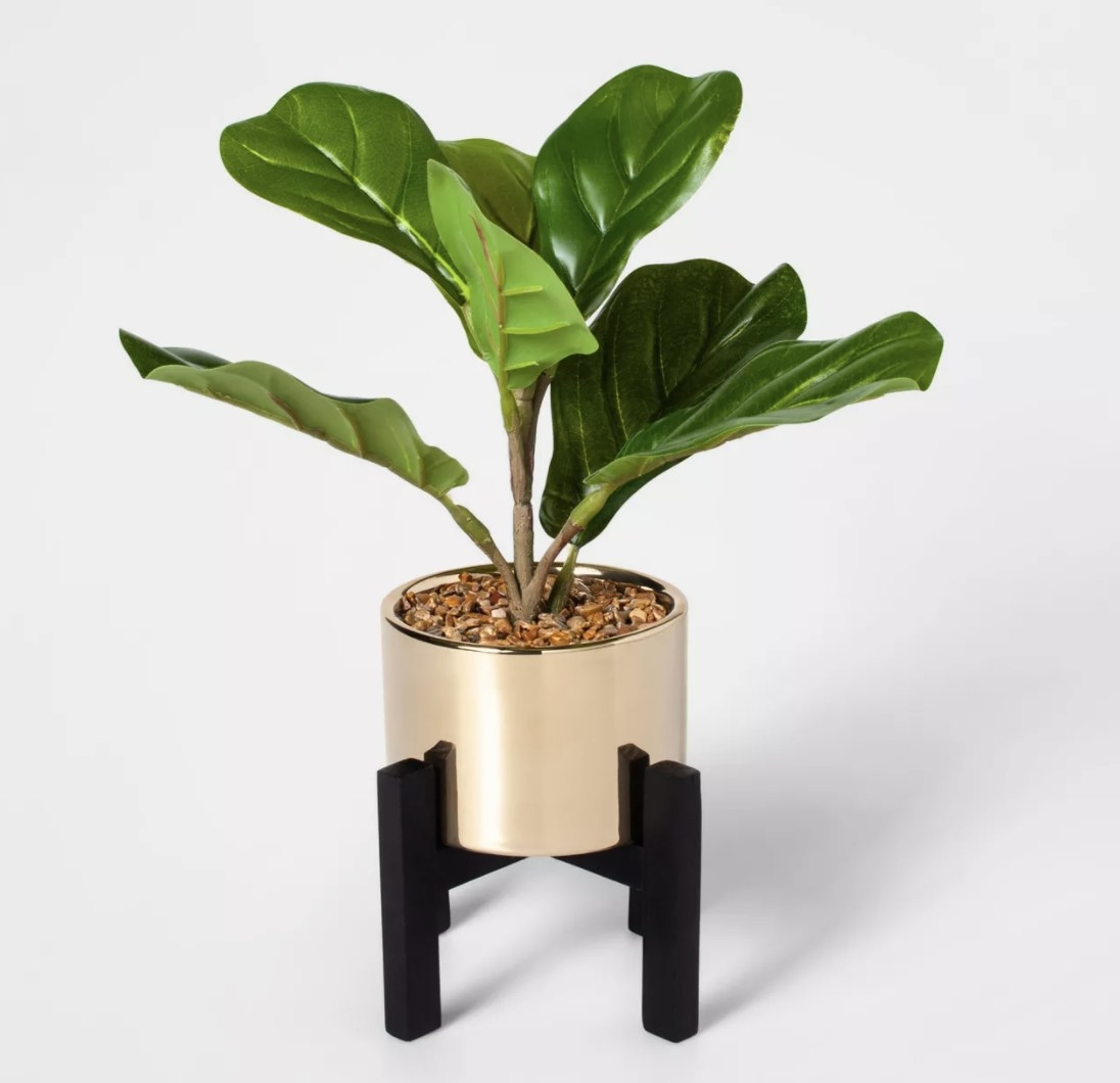 Miniature faux fiddle leaf fig plant in a gold pot with a black stand