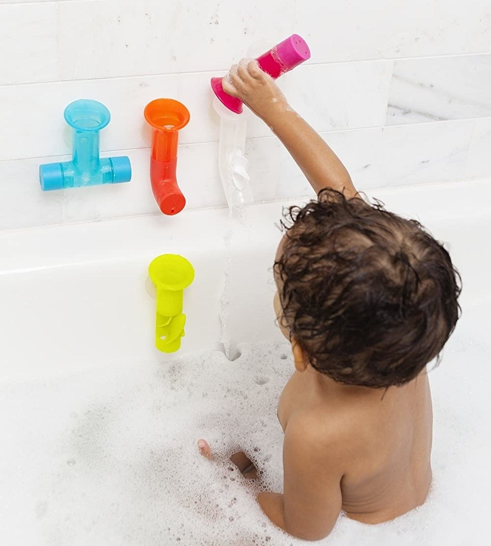 Baby sitting upright and pouring water into pipes attached to bathtub wall