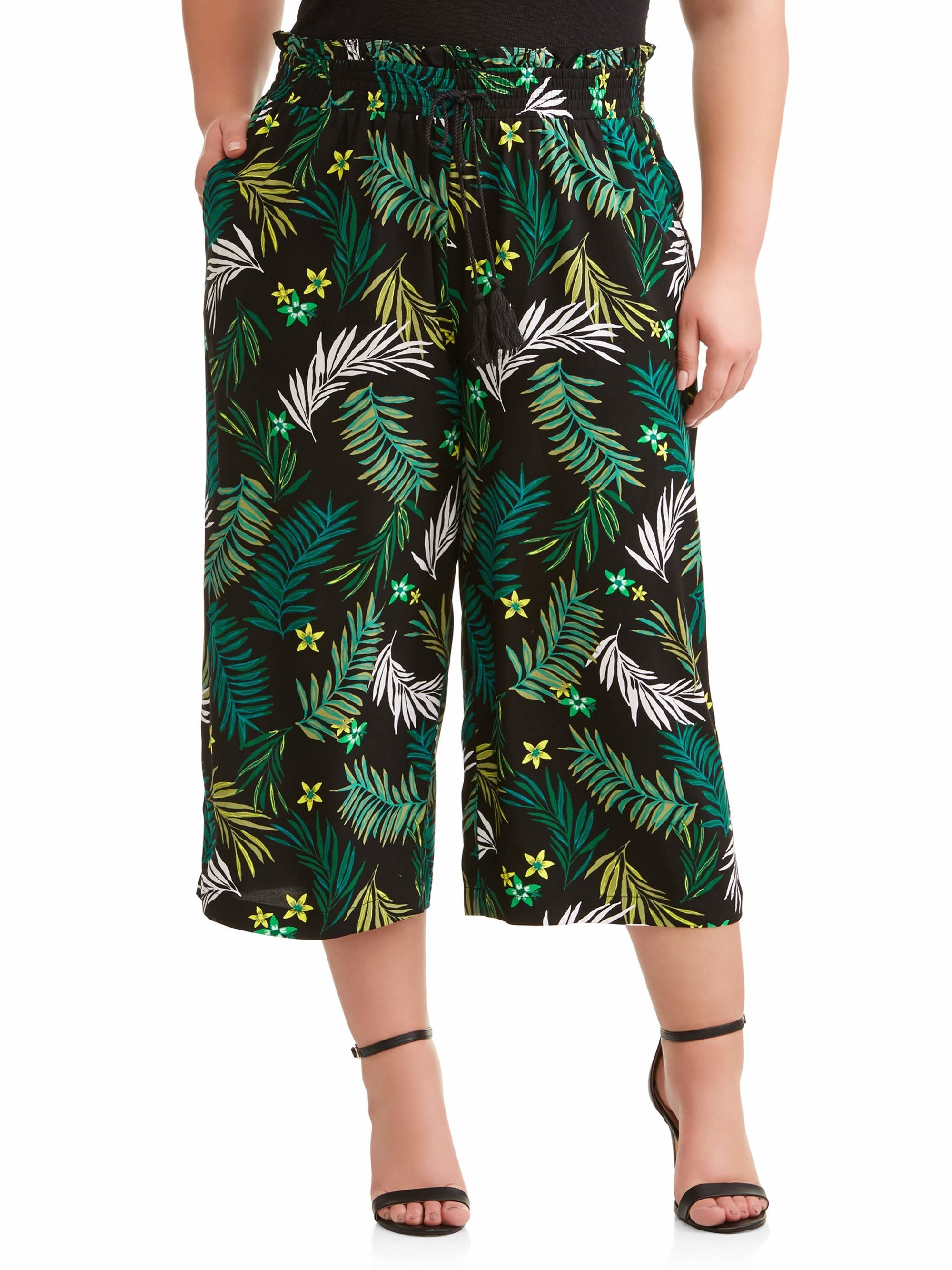 person wearing black flowy pants with a tropical print on them