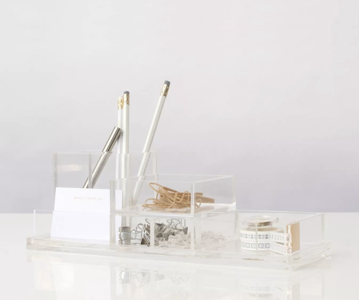Transparent acrylic block holds rubber bands, paper clips and additional desk accessories