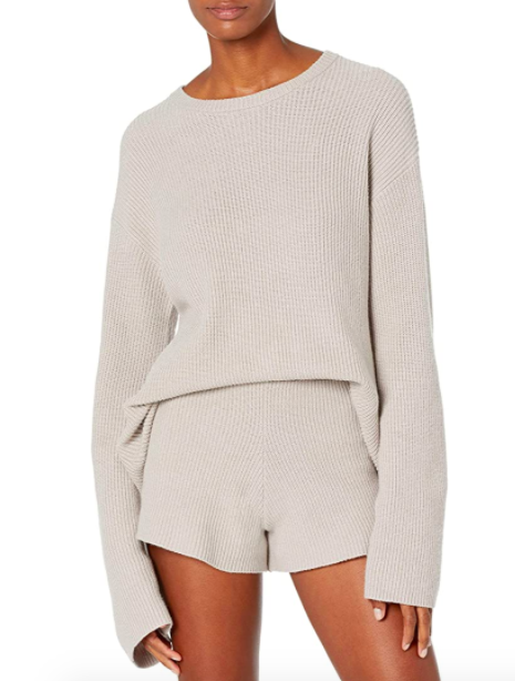A model wears the slouchy sweater over a pair of sweater shorts
