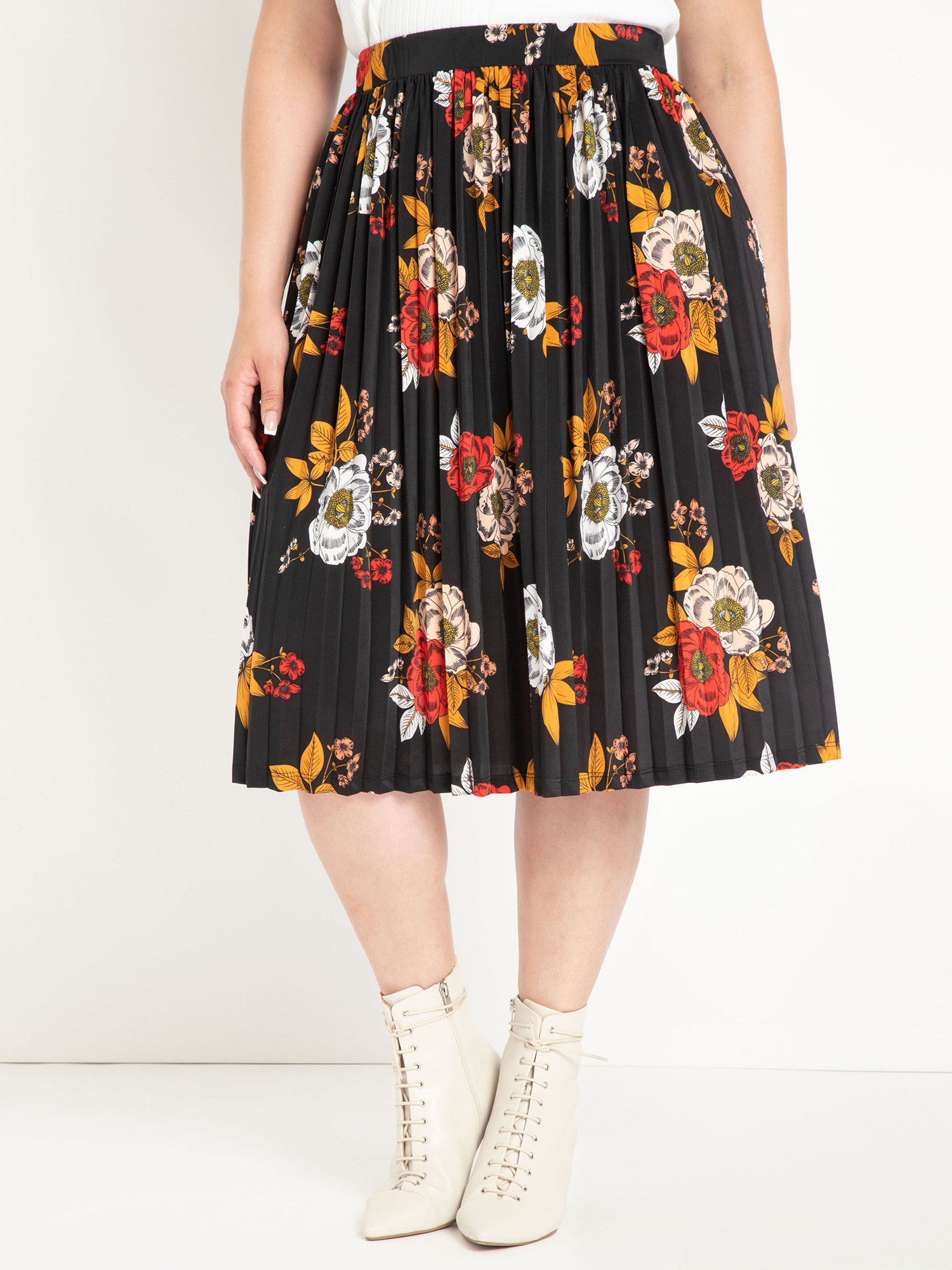 person wearing a pleated black midi skirt with flowers on it