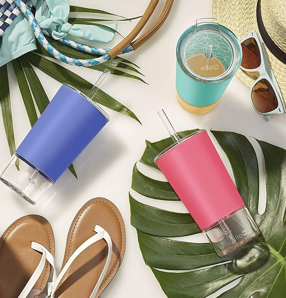 Three glass tumblers surrounded by leaves, sunglasses, and beach accessories