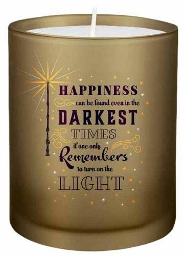 "A golden glass candle inscribed with a quote from the Harry Potter books, ""Happiness can be found even in the darkest times if one only remembers to turn on the light."""