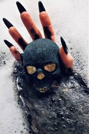 手用长长的指甲,在泡泡浴中持有头骨浴炸弹