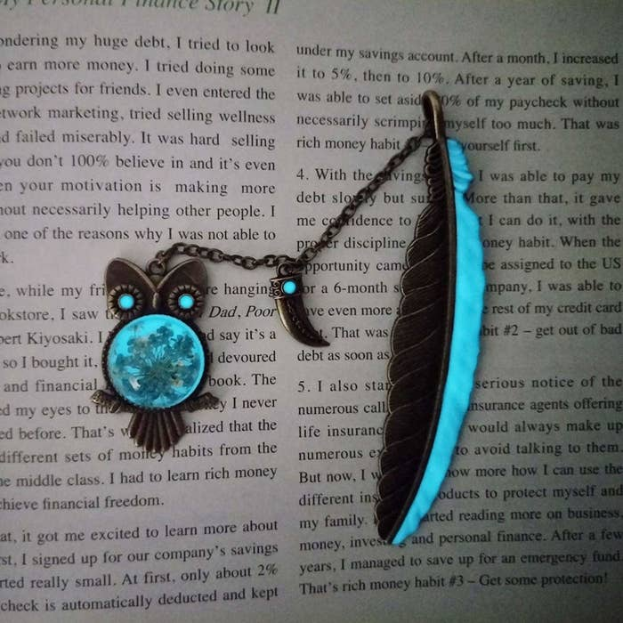 An owl and feather shaped glow-in-the-dark bookmark kept on a text-filled page.