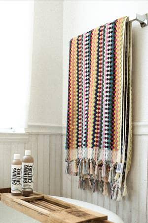 毛巾挂起来,在边缘显示彩虹条纹和三维点和流苏
