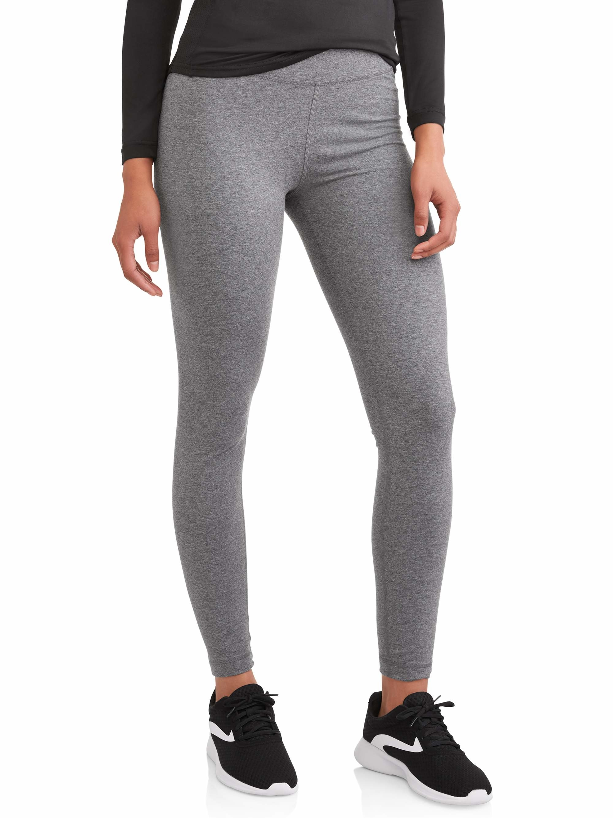 person wearing gray leggings with dark gray top and black sneakers