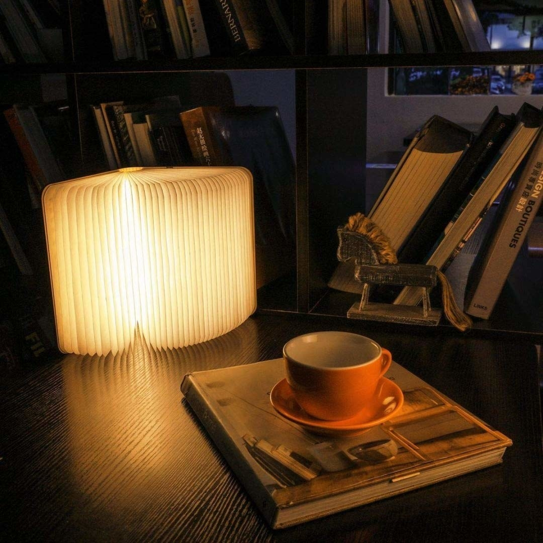 The expanded book-shaped lamp kept on a desk with books and a cup.