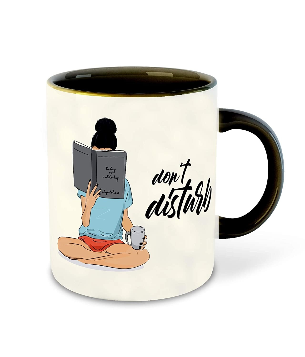 """A white mug printed with a girl reading a book and the phrase, """"don't disturb""""."""