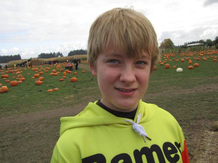 A young boy smiles at the camera in a pumpkin patch