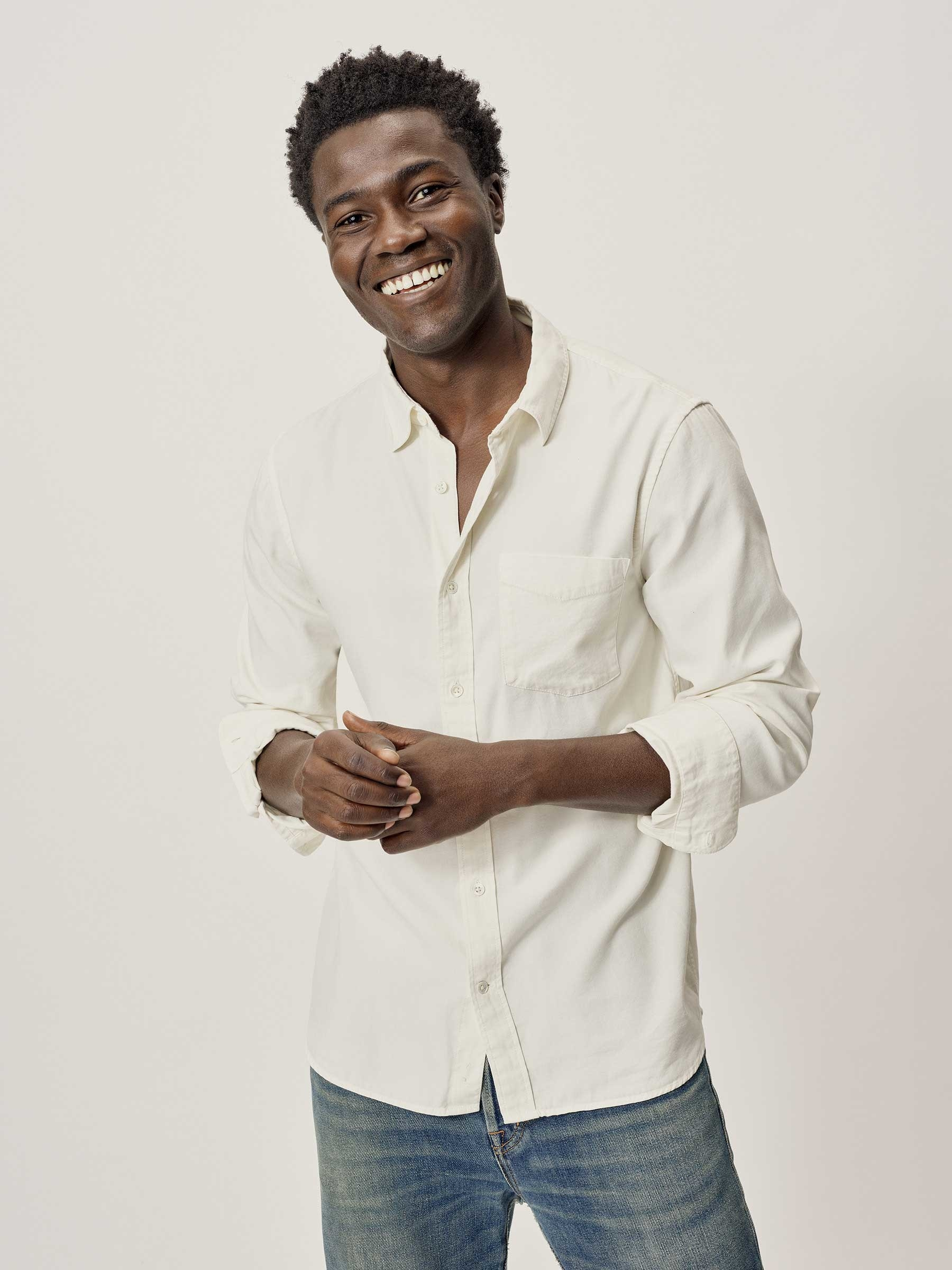 Model wearing Buck Mason natural draped twill one pocket button down shirt in natural