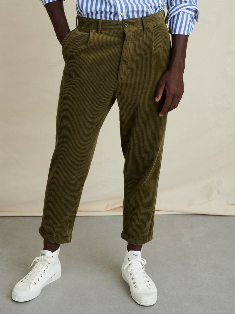 Model wearing Alex Mill rugged cord pleated pant in dark olive