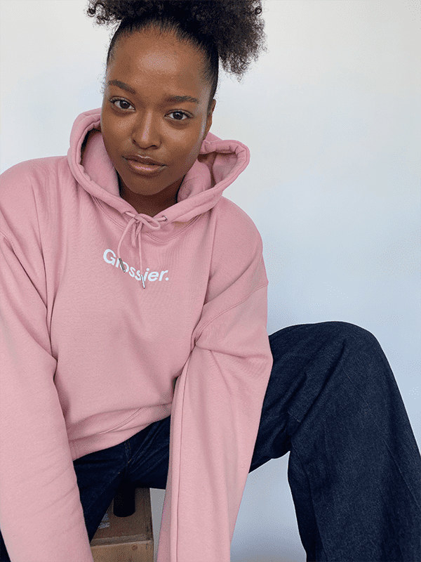 Model wearing the hoodie, featuring the Glossier logo in the front