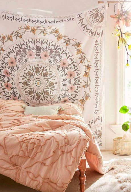 Pink and white floral medallion tapestry hanging above a bed with a pink comforter