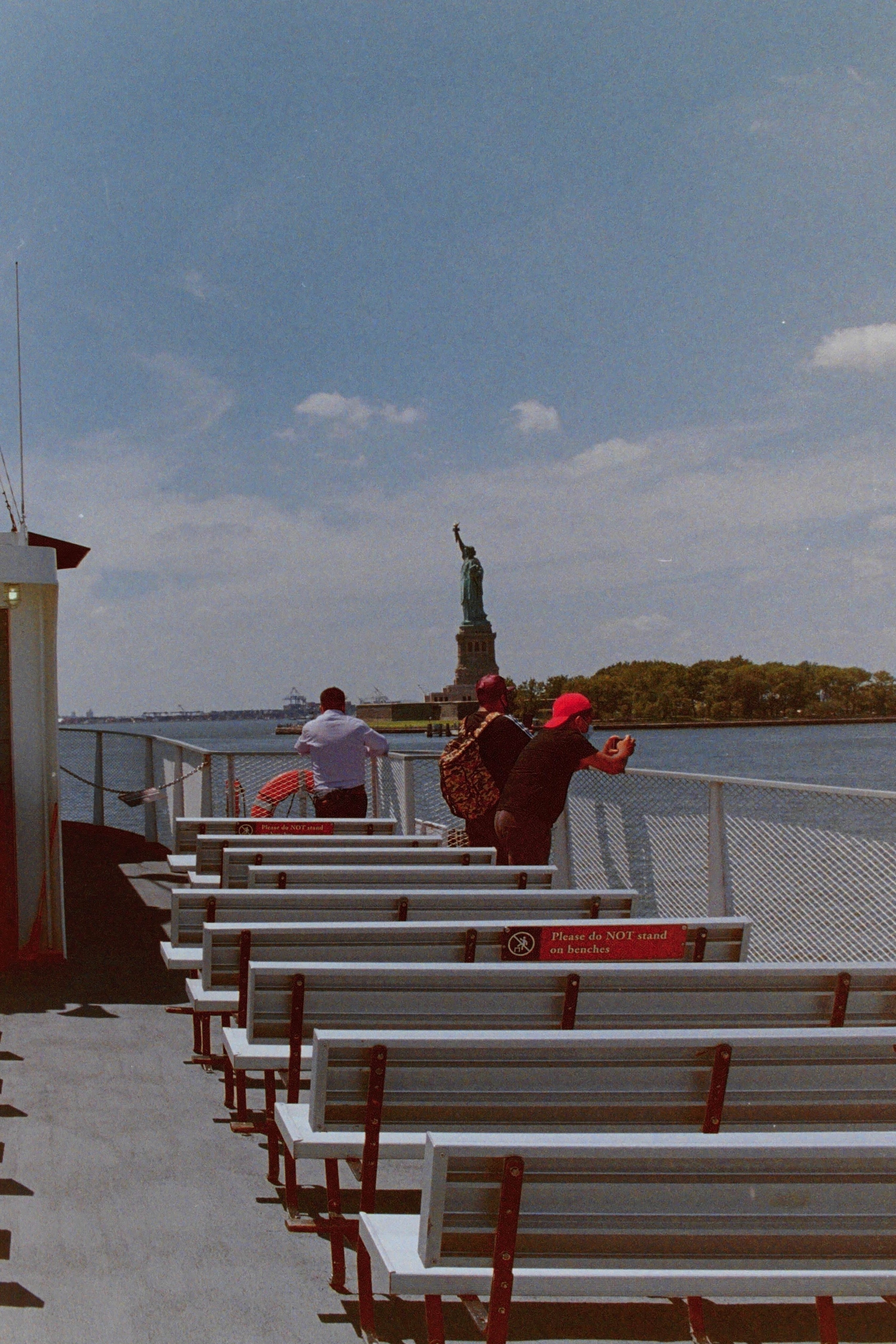 Three people, peering over the water at the Statue of Liberty, stand on a mostly empty ferry