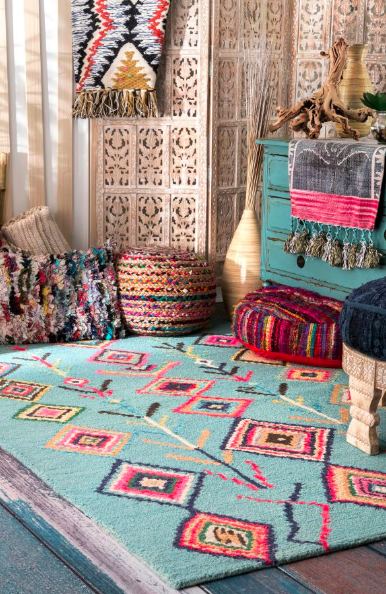 Rectangle-shaped turquoise rug with colorful Moroccan diamonds next to rainbow pouf and blue dresser