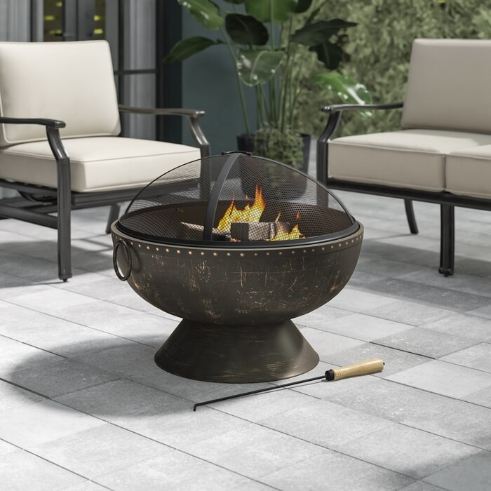 A stainless steel fire pit, lit on a patio.