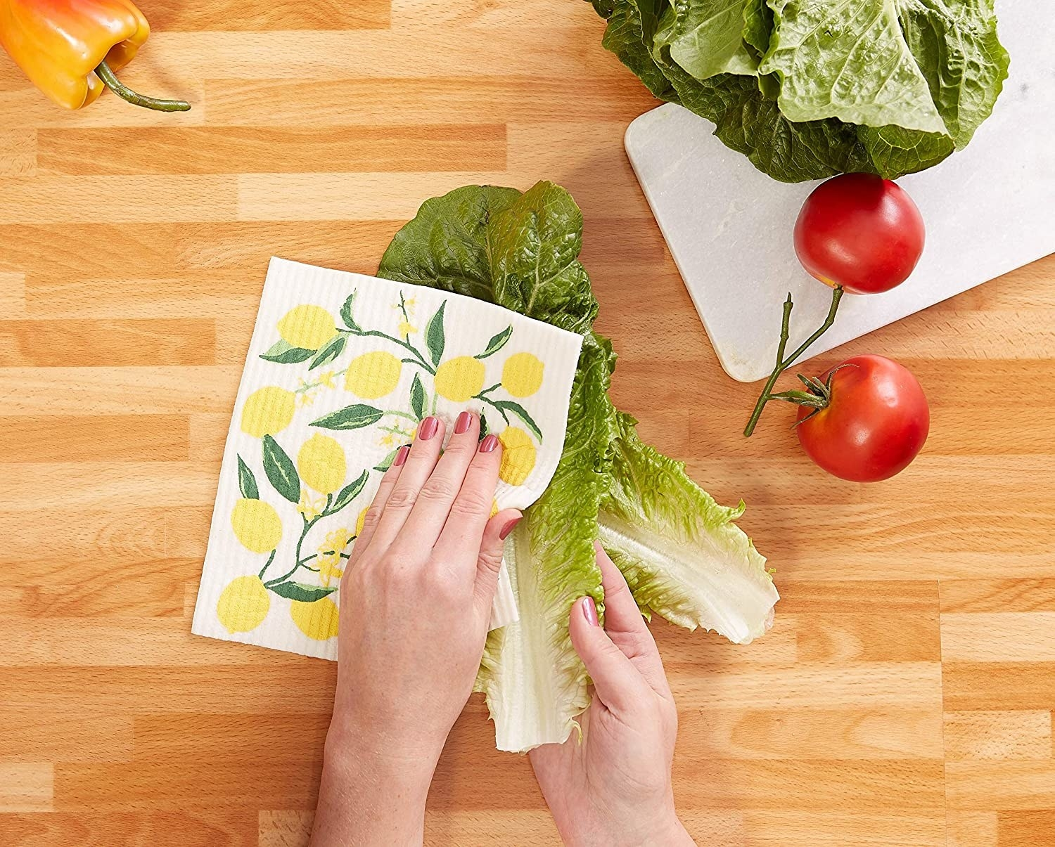 Close up of a model's hands using the dishcloth with a lemon illustration to clean some lettuce.