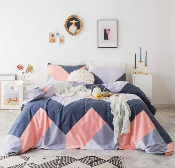 Pink, purple, and navy blue geometric-print bedding with a white accent pillow