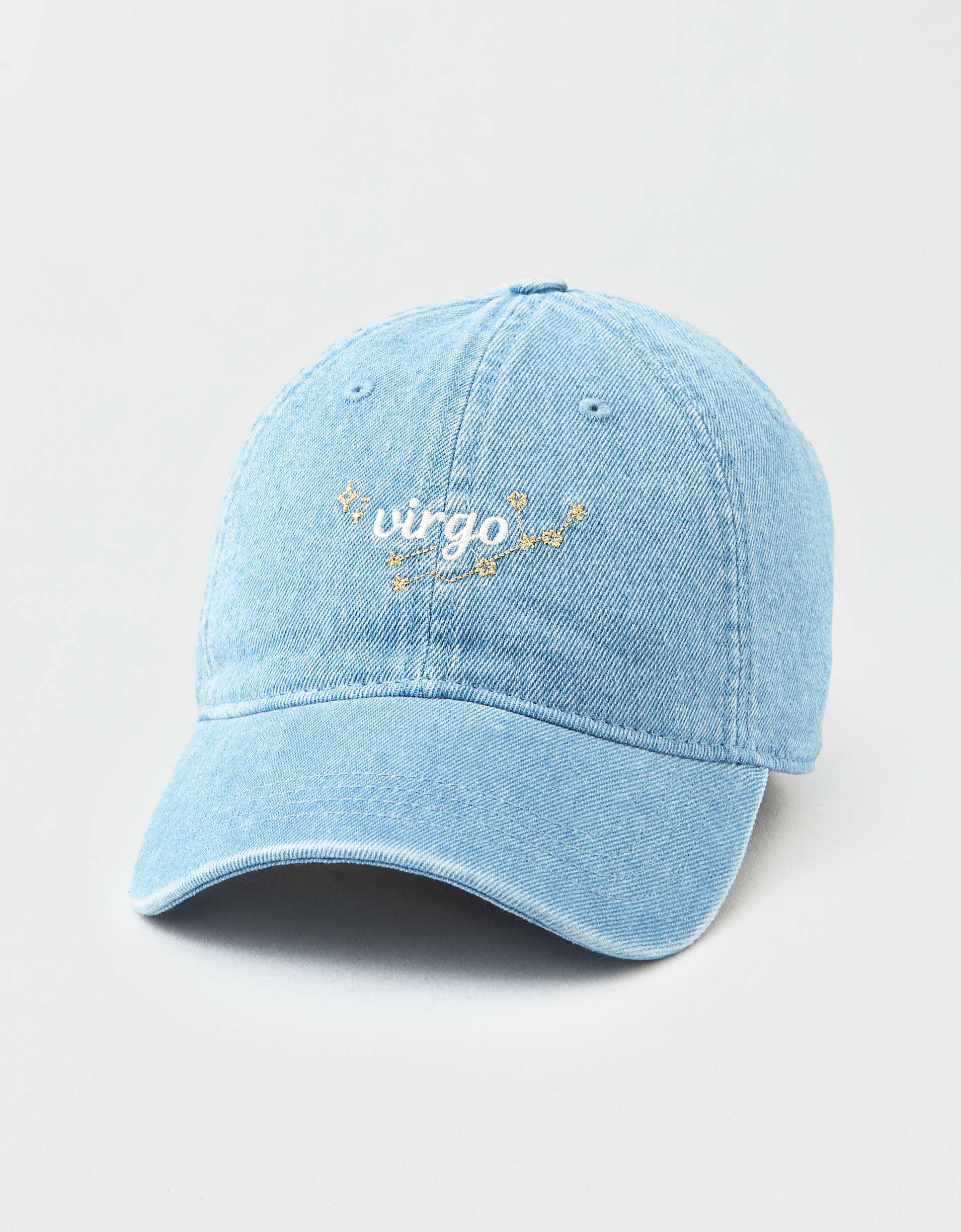A denim baseball cap with 'virgo' written in white cursive font and the virgo constellation behind the text