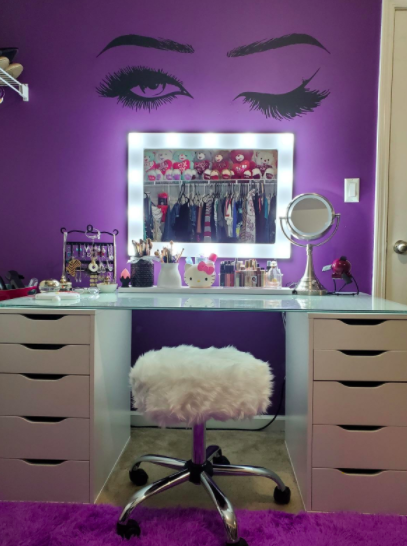 Black and white winking eyes wall decal on a purple wall above a white makeup vanity