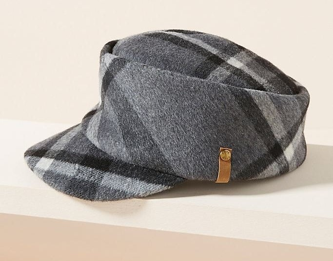 A cap with a cylindrical base and visor extended at a downward angle with a thick, plaid print