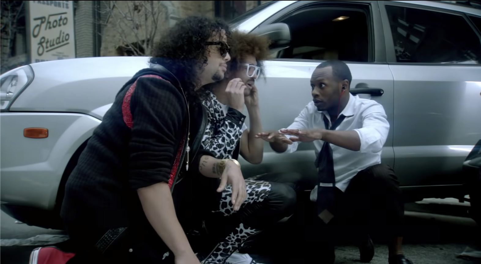 Redfoo, Sky Blu, and Malcolm hiding behind a car.