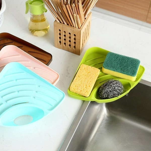 The corner rack pictured on the edge of a sink with dishwashing sponges in it.