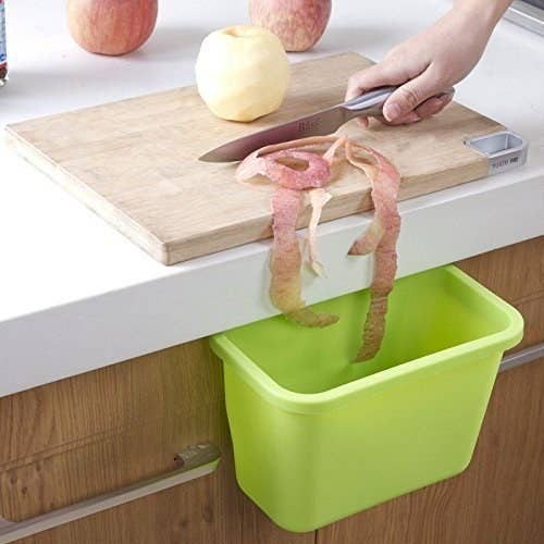 A person scraping apple peel from a chopping board into the over-the-door trash can attached to a shelf below it.