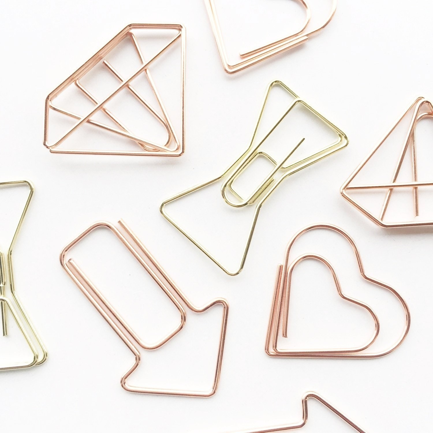 Rose gold paperclips in a variety of shapes - an arrow, a heart, diamond, and hourglass.