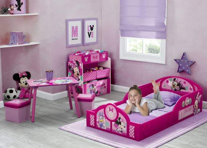 child sitting on a pink bed in a minnie mouse-themed bedroom