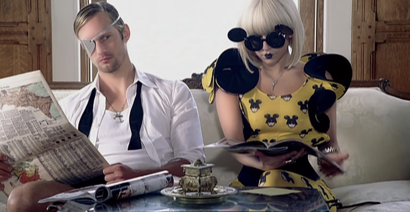 Alexander, in an eye patch, sitting next to an ostentatiously dressed Lady Gaga.