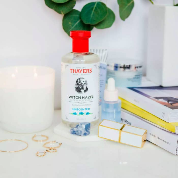 the unscented toner displayed on a desk next to a candle