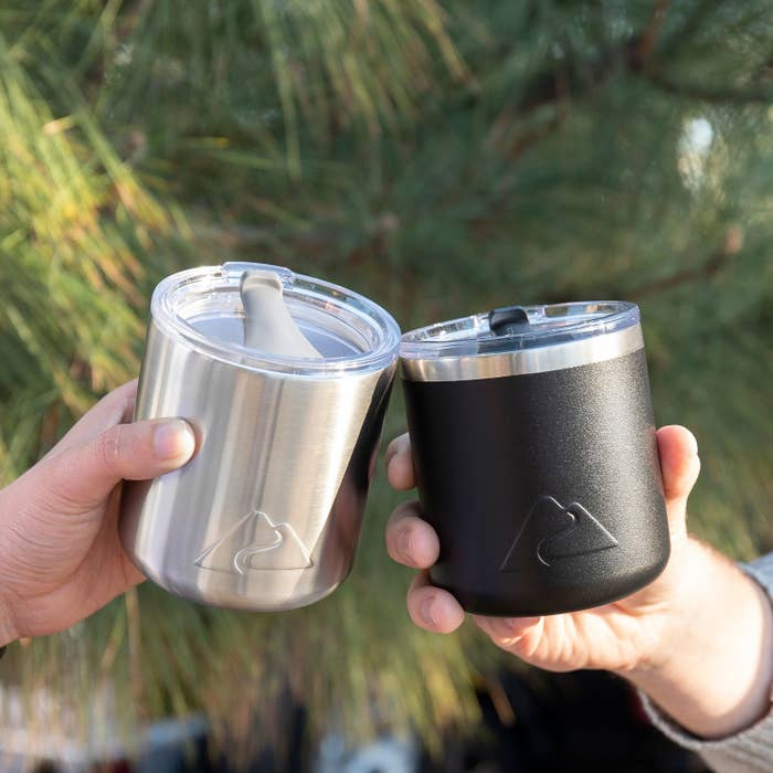 two people holding up stainless steel insulated cups