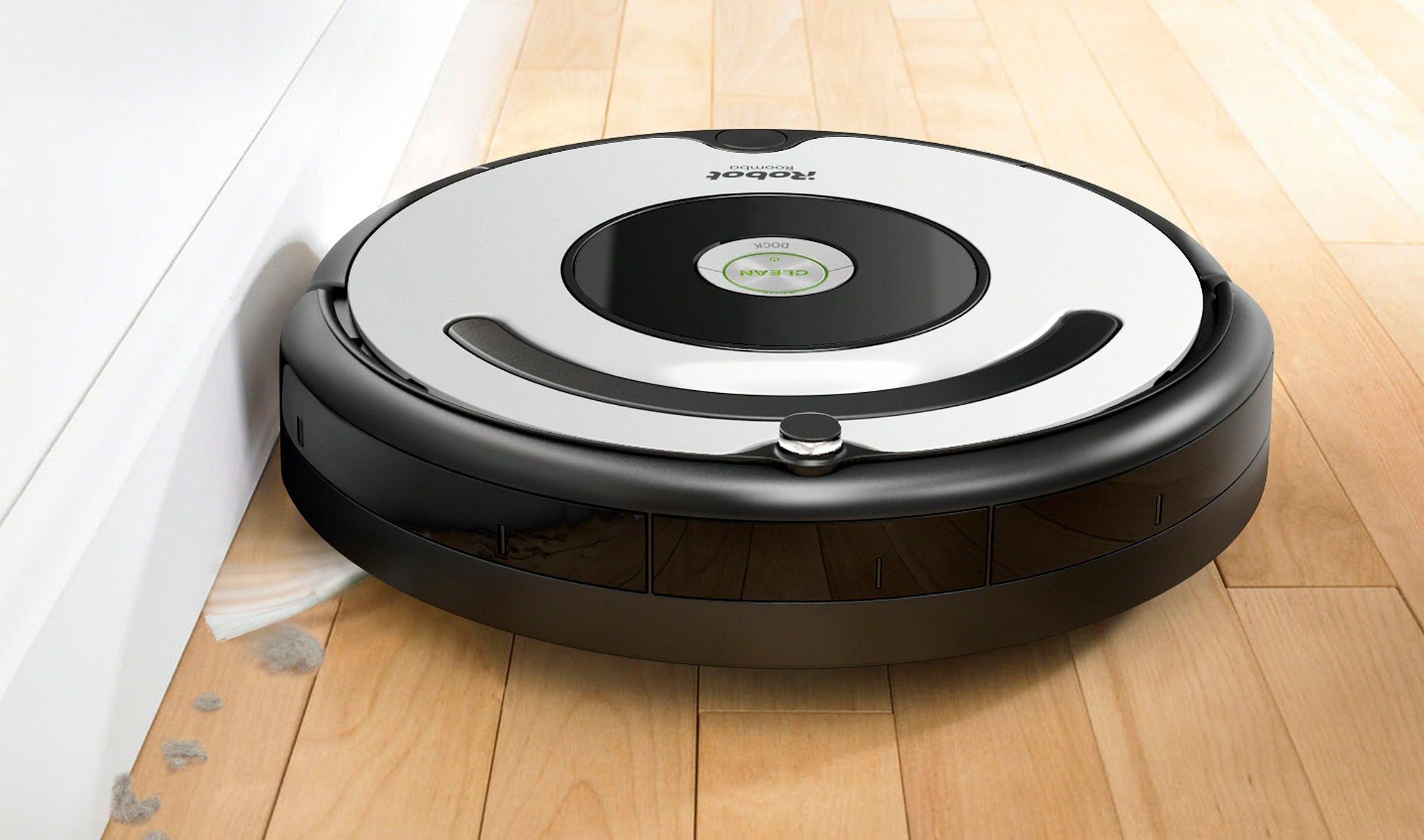 roomba robot vacuum sweeping up dust against a wall